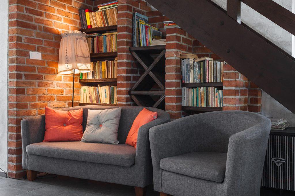 Bild zeigt Sofa und Sessel vor Bücherregal und eine Stehlampe - Bild erzeugt eine warme Atmosphäre